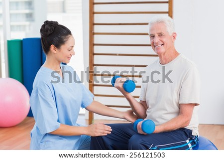 Female instructor assisting senior man in lifting dumbbells at gym