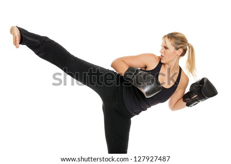 Female kickboxer doing a side kick isolated on a white background