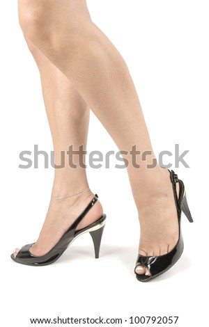 Female legs wearing  black heel shoes over white background
