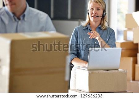 Female Manager Using Headset In Distribution Warehouse