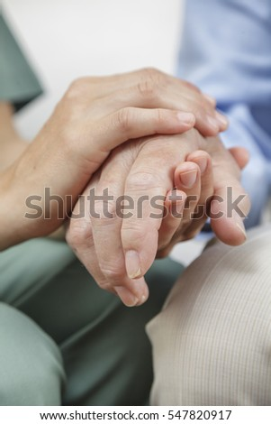 Female nurse holding the hand of a senior man