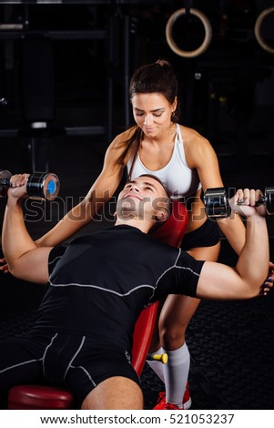 Female personal fitness instructor helping a young man at gym, he exercising with dumbbells on the bech.