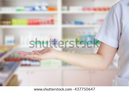 female pharmacist with blur shelves filled with medication in the pharmacy