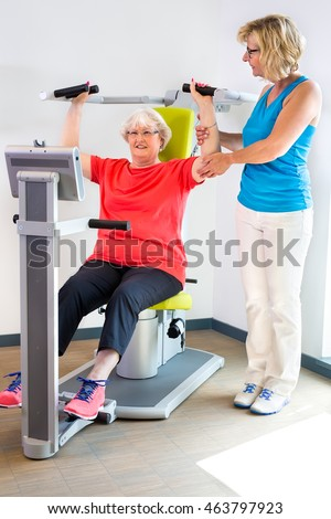 Female physical therapist helping senior patient in glasses with exercises on machine used to increase shoulder strength