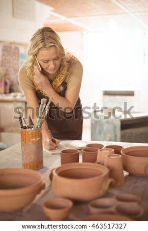 Female potter taking an order on mobile phone in pottery workshop