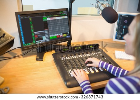 Female radio host in front of screen operating sound mixer at desk in studio