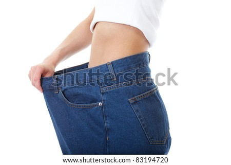 female shows her old huge pair of jeans, weight loss concept, studio shoot,
