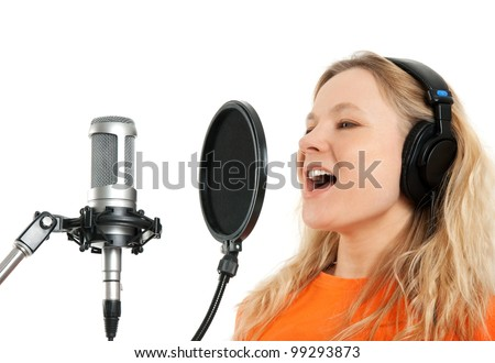 Female singer in headphones singing with studio microphone. Isolated on white background.