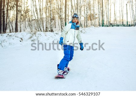 female snowboarder snowboarding down the mountain among the trees at sunset, concept of sport and active lifestyle