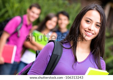 Female student smiling at the university holding notebook
