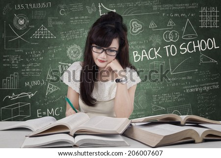 Female student studying at classroom while writing the source on book