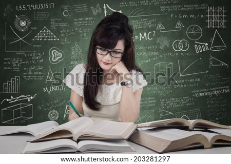 Female student studying at reading room while writing the source on book