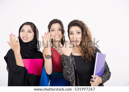 Female students in traditional dresses from different cultures on white background