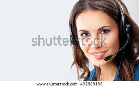 Female support phone operator in headset, on grey background, with blank copyspace area for advertising slogan or text message. Caucasian brunette model in help servise and client consulting concept.