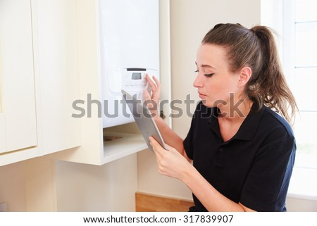 Female technician servicing boiler� using tablet computer