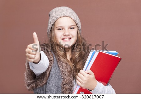 Female teen student thumbs up against brown background