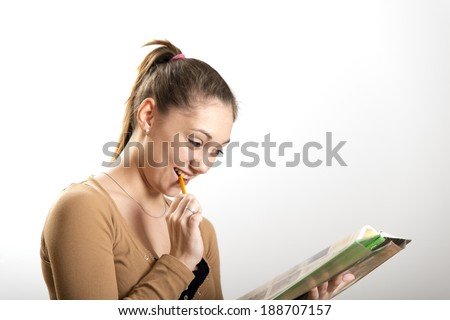 Female teenager studying with pencil and book