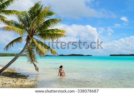 Female tourist bathing in the shallow water of the sea under a hanging palm tree on a beach on a desert island in the lagoon of Rangiroa, a tropical atoll near Bora Bora in pacific  French Polynesia.