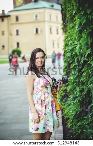 Female tourist takes picture in historic city in Cracow, Poland.