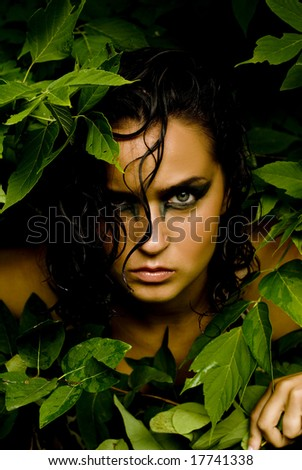 Female with dark eye shadow posing with leaves framing her face
