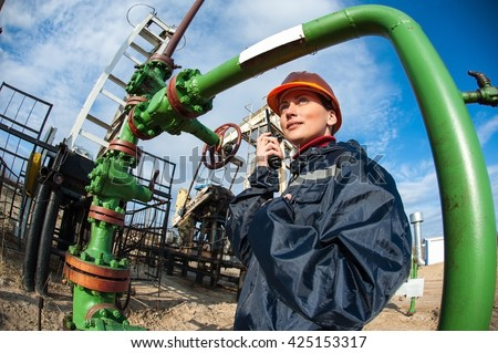 Female worker in the oil field talking on the radio wearing orange helmet and blue work clothes. Industrial site background.