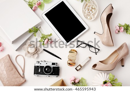 female workspace with tablet, high heels, photo camera and office supplies  on white background. Flat lay, top view office table desk.