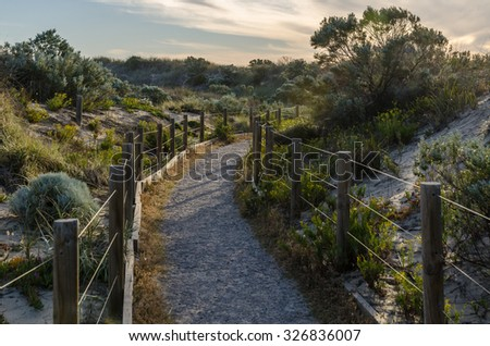 Fenced walkway through sand dunes at sunset