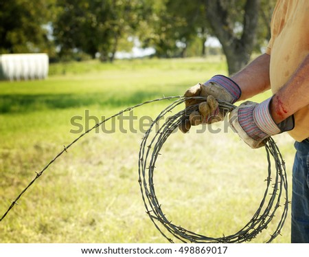 Fencing and safety: Man's hands working on barbed wire farm fence with blood cut.