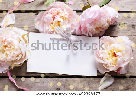 Festive background with sweet pink peonies flowers  and empty tag. Flat lay. Top view with place for text. Selective focus.