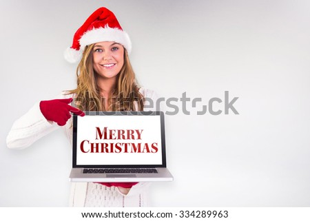 Festive blonde pointing to laptop against grey background