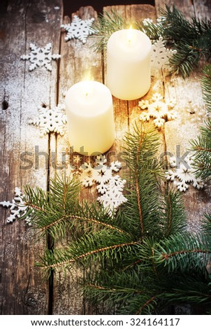 Festive Burning Candles with Christmas Decor Snowflakes and Green Fir Tree on Wooden Background. Vintage style