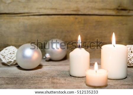 Festive christmas decoration in white, lightning candles, wooden backgound and christmas balls