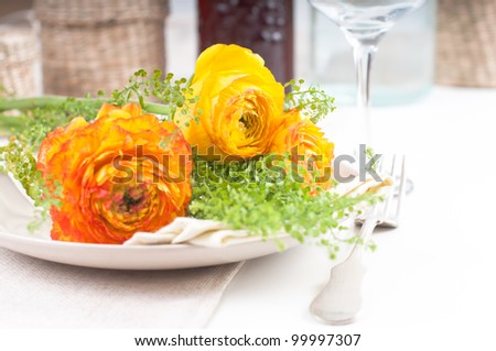 festive dining table setting with yellow-orange flowers ranunkulus