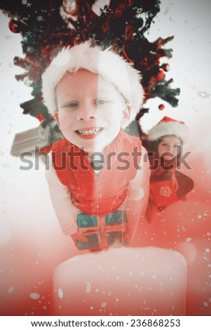 Festive little siblings smiling at camera holding gifts against candle burning against festive background
