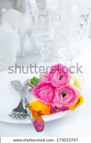 Festive table setting with a bouquet of colorful buttercups flowers, vintage crockery and cutlery, wedding party, close up