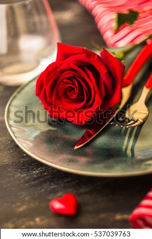 Festive table setting with red rose and heart on dark rustic table with copyspace