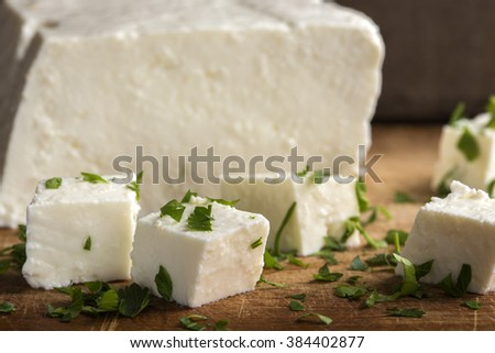 Feta cheese cubes and parsley on a wooden background