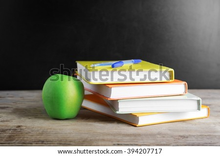 Few books with pen and green apple on table