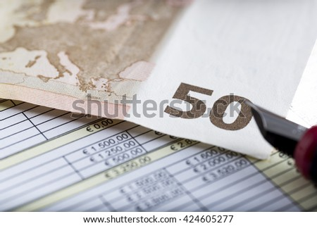 Fifty Euro Banknote in a macro shot, with below chart and sheet accounts, concept to look for the best stock market investment