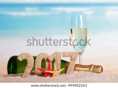 Figures 2017, a bottle of champagne and glass, starfish in the sand against the sea.