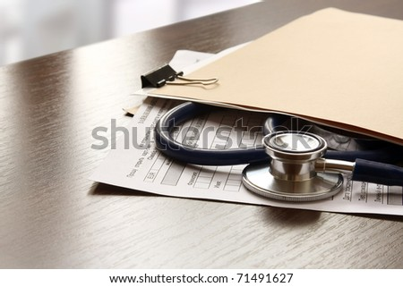 File folder with blank label for text and medical stethoscope