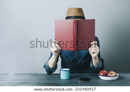 filtered photo of a young hipster man reading a book and relaxing
