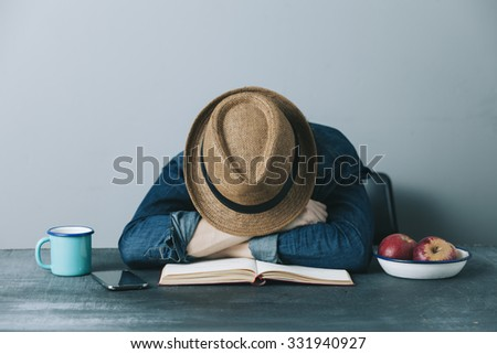 filtered photo of a young tired hipster man having a nap on the desk