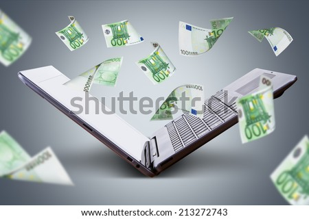 Finance and earning concept, one hundred euro banknotes flying around laptop, internet, side view on dark background.