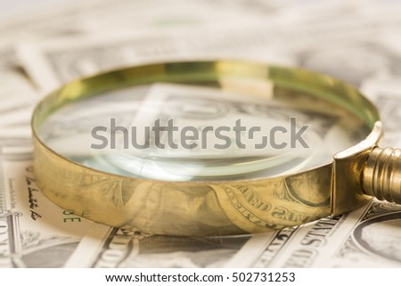Finance concept. Gold magnifying glass on dollar banknotes. Selective focus.