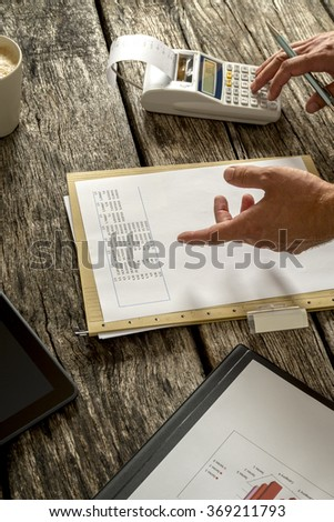 Financial adviser or accountant checking statistical data and numbers while making calculations using desk calculator.