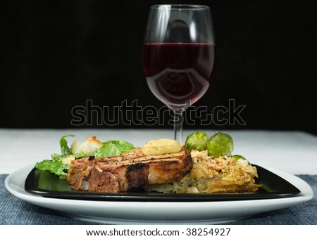 Fine Dining, Gourmet grilled pork loin with scalloped potatoes, Brussels sprouts, Caesar salad, hot mustard, and red wine