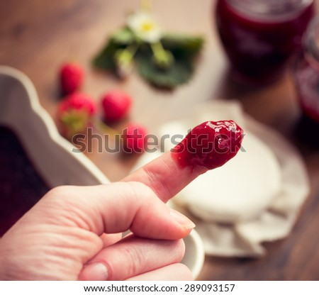 Finger dipped in strawberry jam. Homemade strawberry jam (marmalade) concept.
