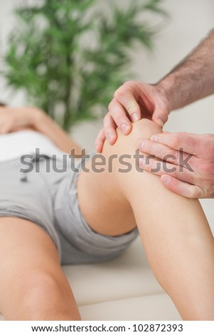 Fingers of a doctor massaging a leg in a room