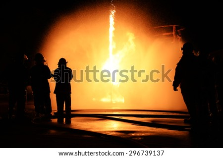 Firefighters fighting a fire. At night